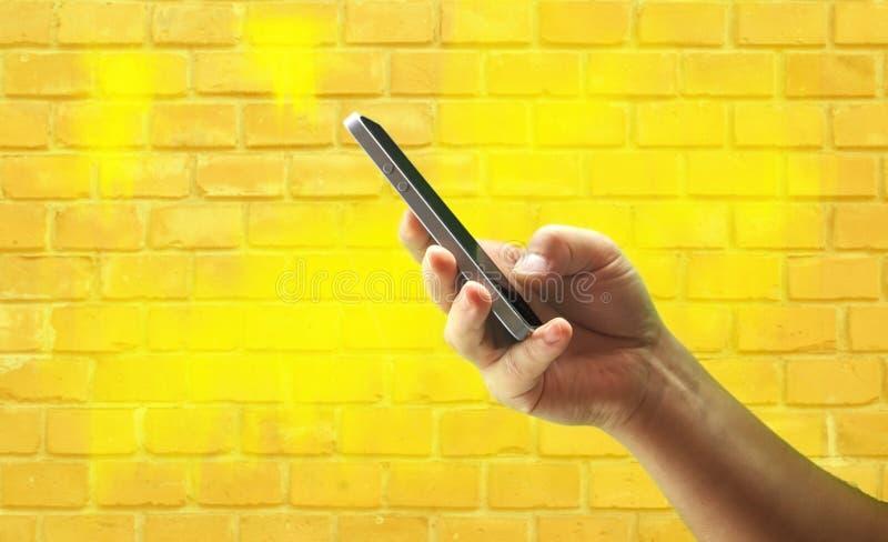 Ungt mans den hållande mobiltelefonen för handen mot den gula tegelstenväggen arkivfoto