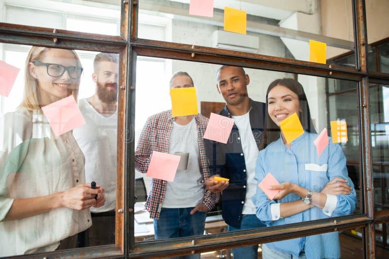 Ungt modernt folk i smarta tillfälliga kläder genom att använda självhäftande anmärkningar, medan stå bak glasväggen i bräderumme fotografering för bildbyråer