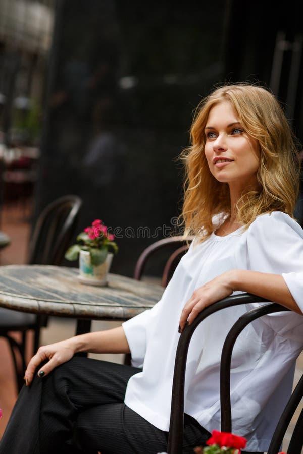 Ungt nätt blont kvinnasammanträde i kafé i dag arkivfoto