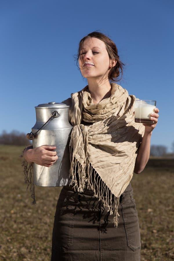 Ungt nätt bondaktigt dricka för kvinna som är nytt, mjölkar royaltyfri fotografi