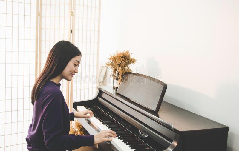 Ungt nätt härligt asiatiskt flickasammanträde på pianot royaltyfri bild