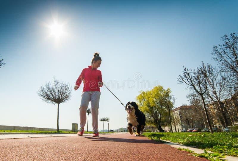 Ungt nätt köra för flicka som är utomhus- med hennes hund för Bernese berg royaltyfri foto
