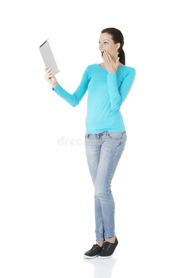 Ungt nätt kvinnaarbete på tabletdatoren royaltyfri foto