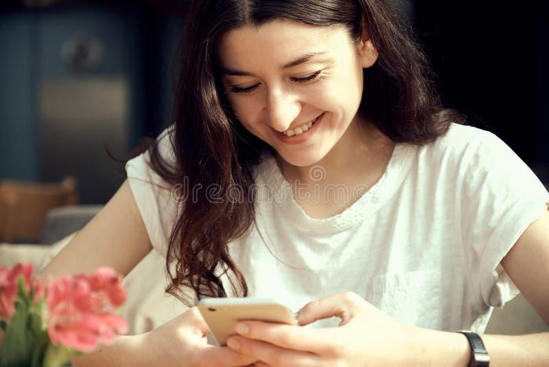 Ungt nätt kvinnainnehav och användasmartphone och att bläddra internet som direktanslutet pratar, royaltyfri foto