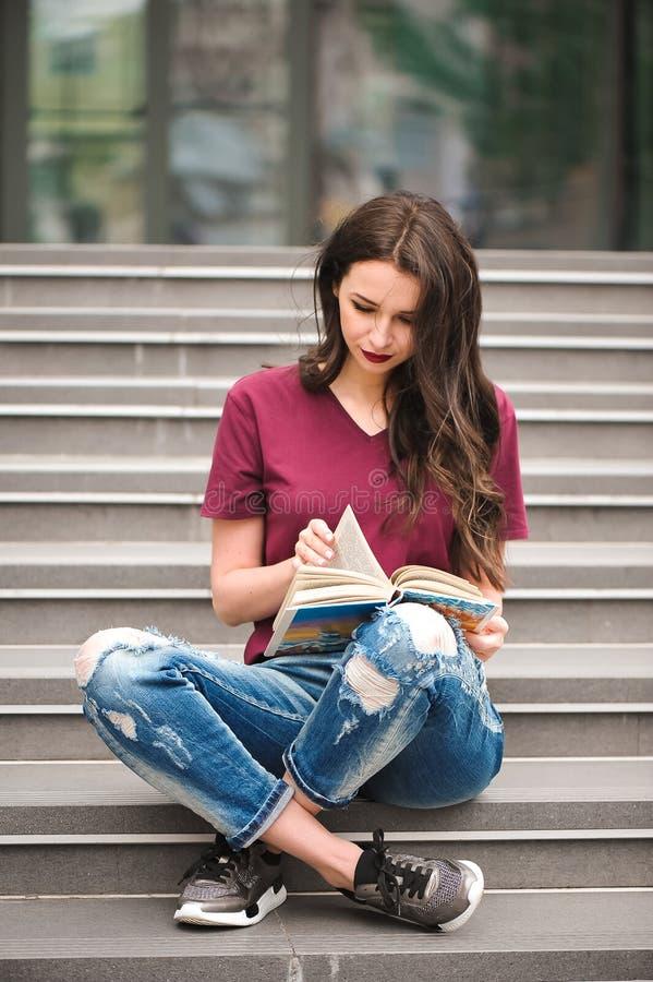 Ungt nätt kvinnasammanträde och läsning som en bok tycker om av vilar royaltyfria bilder