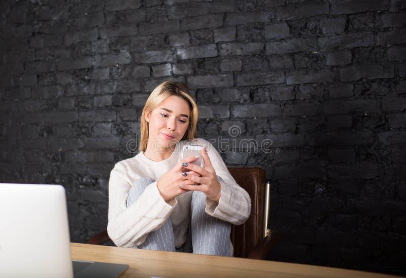 Ungt nätt meddelande för text för kvinnastudent läs- på mobiltelefonen efter arbete på bärbar datordatoren royaltyfria bilder