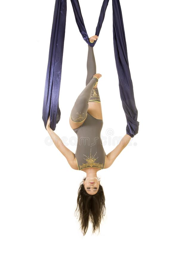 Ungt och att le akrobaten, med l?ngt h?r, i en gr? dr?kt och damasker som g?r ?vningar p? bl?tt luftigt silke fotografering för bildbyråer