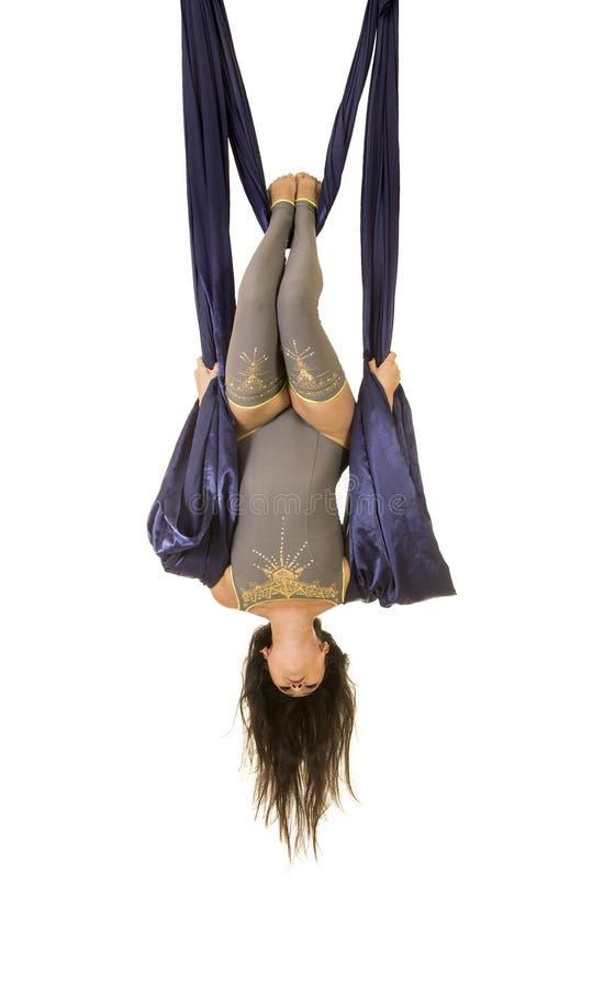 Ungt och att le akrobaten, med l?ngt h?r, i en gr? dr?kt och damasker som g?r ?vningar p? bl?tt luftigt silke arkivfoton