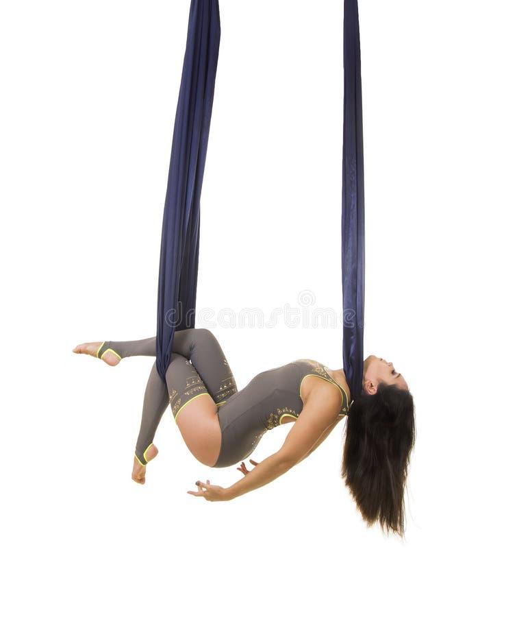 Ungt och att le akrobaten, med l?ngt h?r, i en gr? dr?kt och damasker som g?r ?vningar p? bl?tt luftigt silke royaltyfria bilder