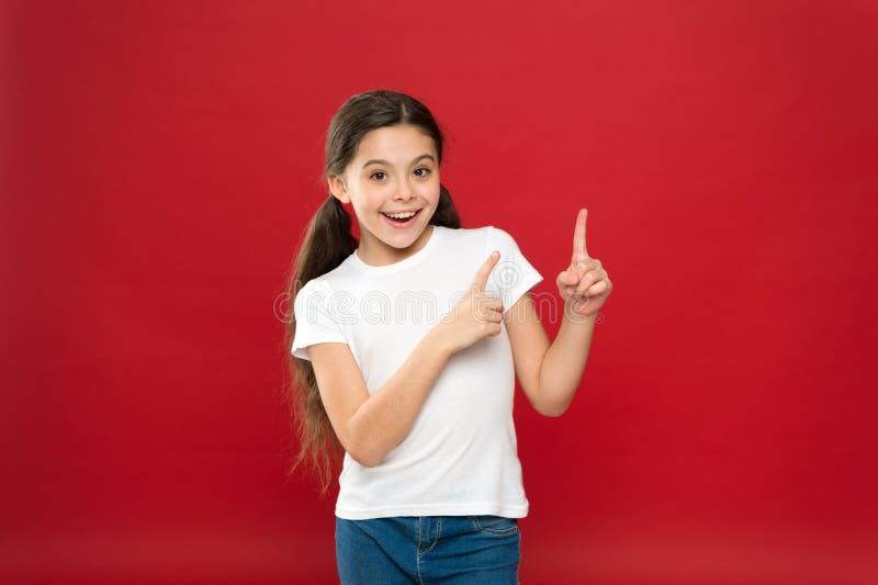 Ungt och fritt Lycklig barnflicka med långt hår på röd bakgrund Lycka och glädje positiva sinnesrörelser Barnavård och royaltyfri fotografi