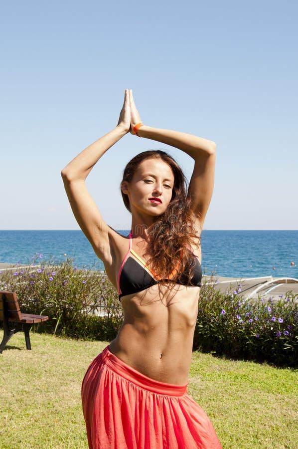 Ungt och fritt Sinnlig flicka pÃ¥ havsstranden östlig skönhet Sommarsemester och lopp solbränna Kvinnadans med kroppen royaltyfri fotografi