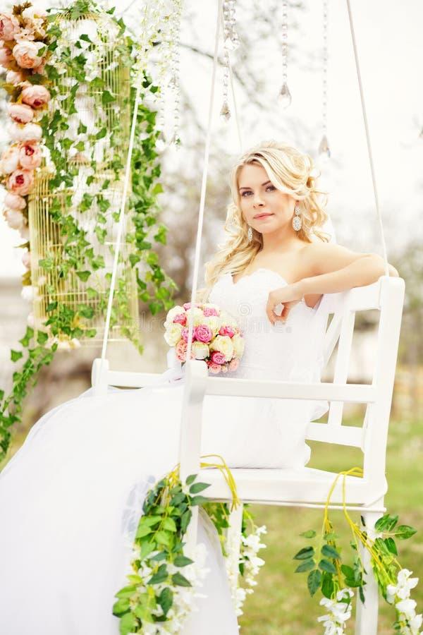 Ungt och härligt brudsammanträde på en vit gunga i ett vårG royaltyfri bild