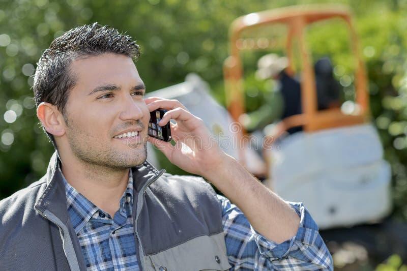 Ungt och le jobbaren på telefonen arkivfoto