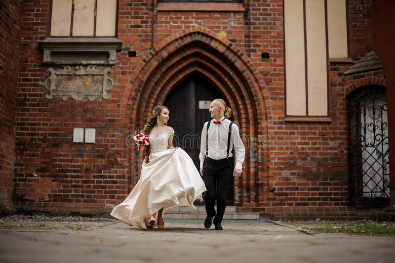 Ungt och lyckligt gift par som går i en gård av gammal byggnad för röd tegelsten för tappning royaltyfria foton