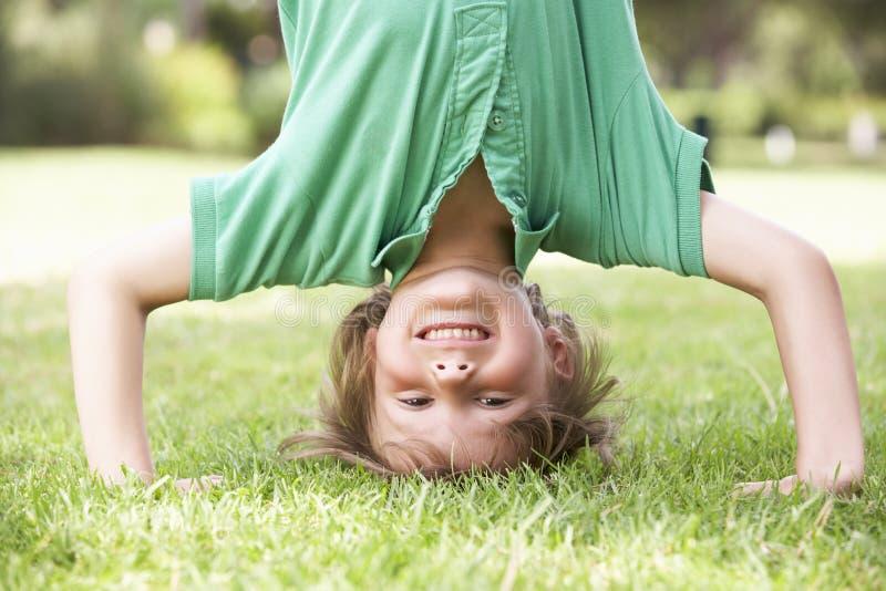 Ungt pojkeanseende på huvudet i trädgård arkivfoton