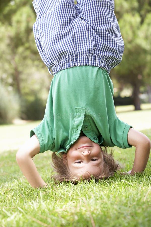 Ungt pojkeanseende på huvudet i trädgård fotografering för bildbyråer