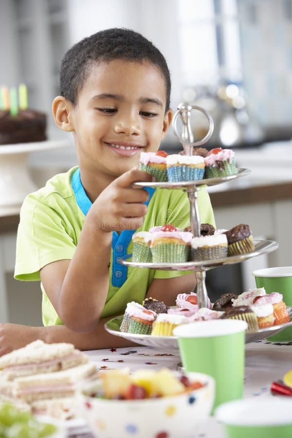 Ungt pojkeanseende vid tabellen som läggas med mat för födelsedagparti royaltyfri bild