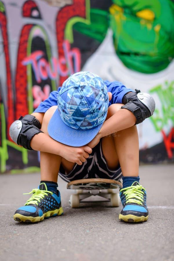 Ungt pojkesammanträde som vilar på hans skateboard royaltyfria foton