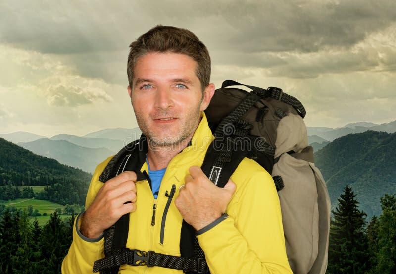 Ungt posera för ryggsäck för lycklig och attraktiv fotvandrareman som bärande är gladlynt under bergvandringen som ler tycka om h fotografering för bildbyråer