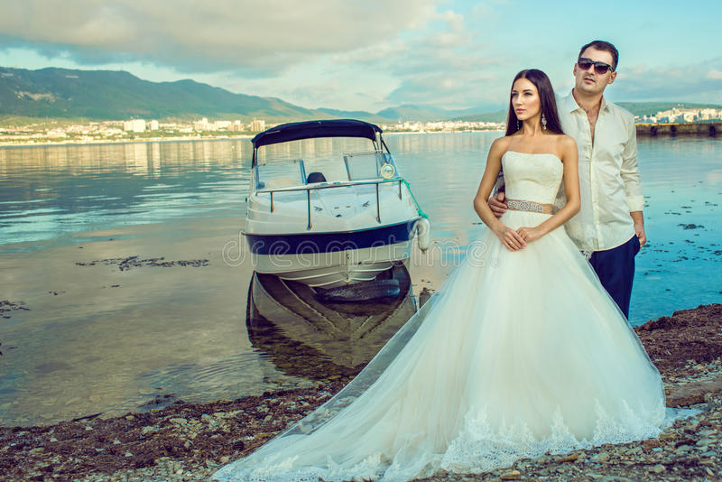 Ungt precis gift par i bröllopkappa och dräktanseende nära fartyget på sjösidan som åt sidan ser royaltyfri bild