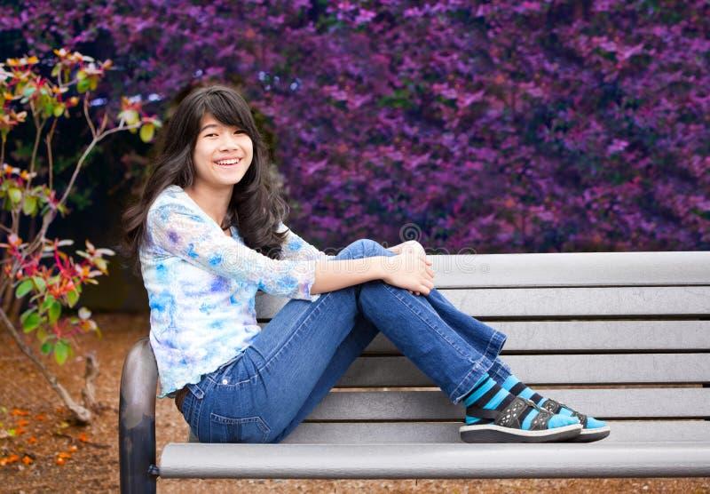 Ungt preteenflickasammanträde parkerar på bänken utomhus fotografering för bildbyråer