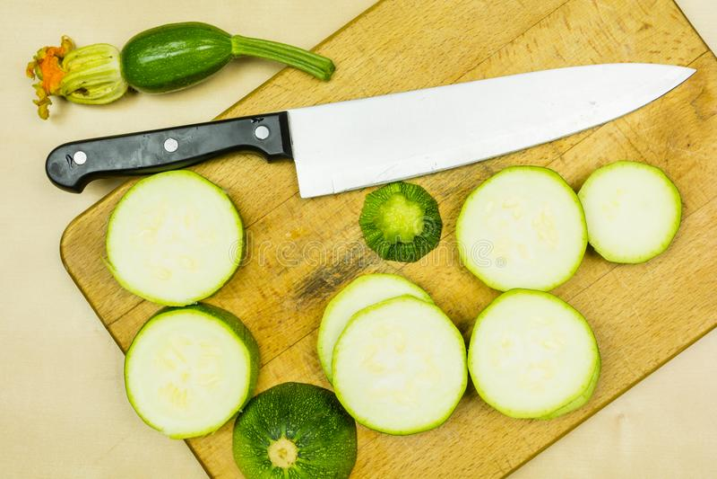 Ungt rått zucchinisnitt in i skivor och en kökkniv på en skärbräda arkivbild