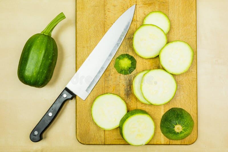 Ungt rått zucchinisnitt in i skivor på en skärbräda royaltyfri foto