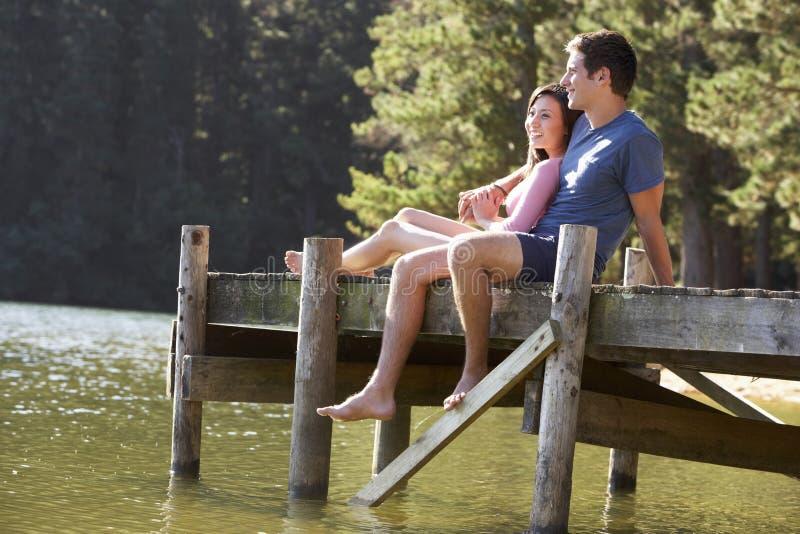 Ungt romantiskt parsammanträde på träbryggan som ut ser över sjön arkivfoto
