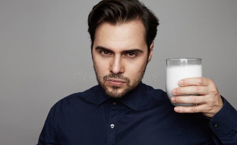 Ungt säkert exponeringsglas för maninnehavhanden av nytt mjölkar på grå bakgrund arkivbilder