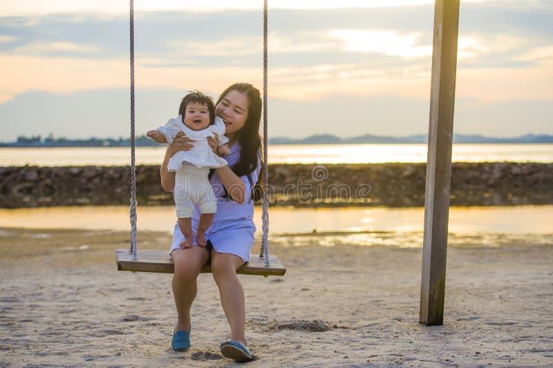Ungt sött och lyckligt asiatiskt kinesiskt rymma för kvinna behandla som ett barn flickan som tillsammans svänger på strandgunga  royaltyfri fotografi