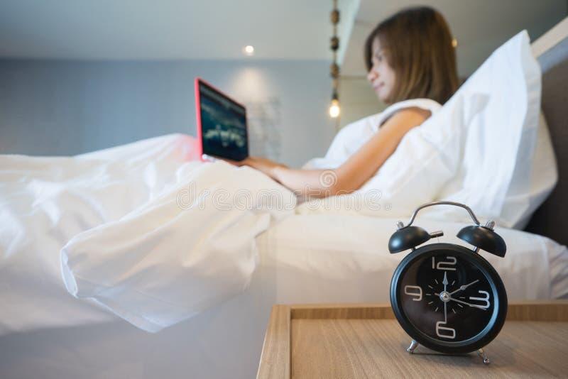 Ungt sammanträde för affärskvinna i vit säng som arbetar på bärbar datordatoren med ringklockan på förgrund royaltyfria bilder