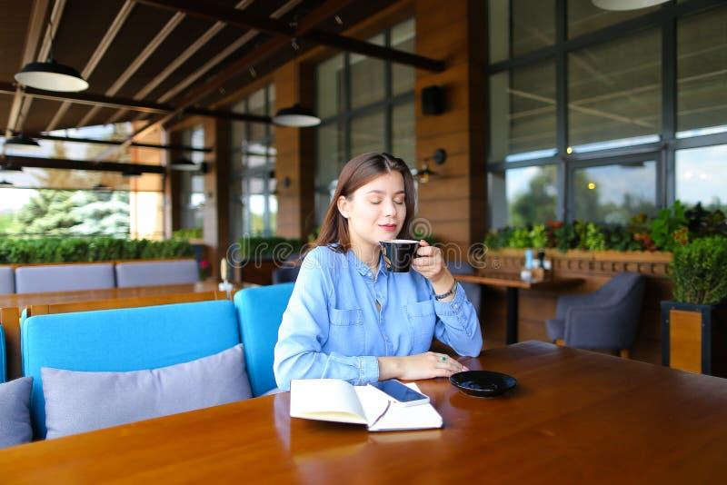 Ungt sammanträde för kvinnlig person på kafét med smartphonen och anteckningsboken och drickakaffe arkivfoton