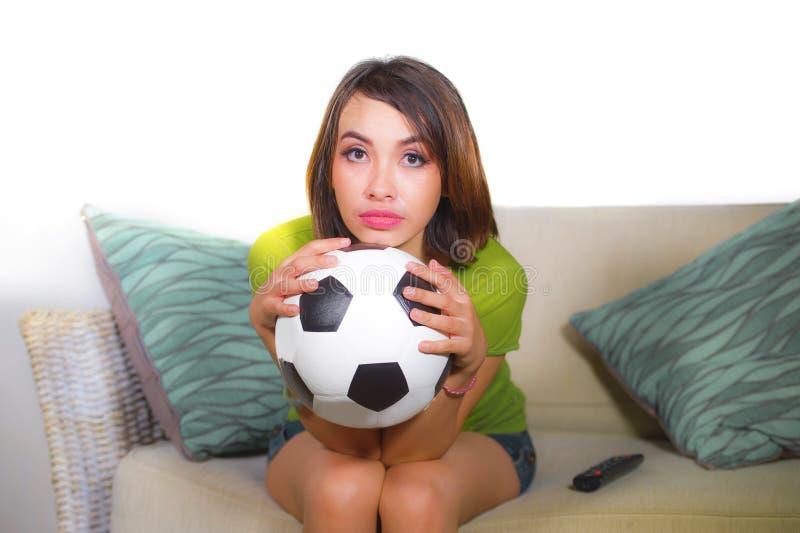 Ungt sammanträde för television för nervös och härlig fotbollsfankvinna hållande ögonen på modigt på boll för fotboll för soffaso royaltyfria foton