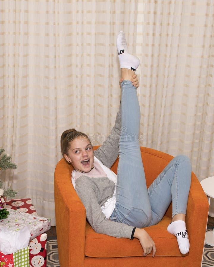 Ungt sammanträde för tonårs- flicka i en orange stol med det högra benet som pekar till taket fotografering för bildbyråer