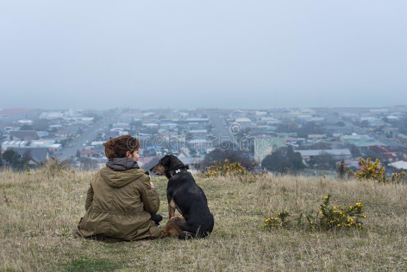 Ungt sammanträde för vuxen kvinna med hennes hund på kullen royaltyfri foto