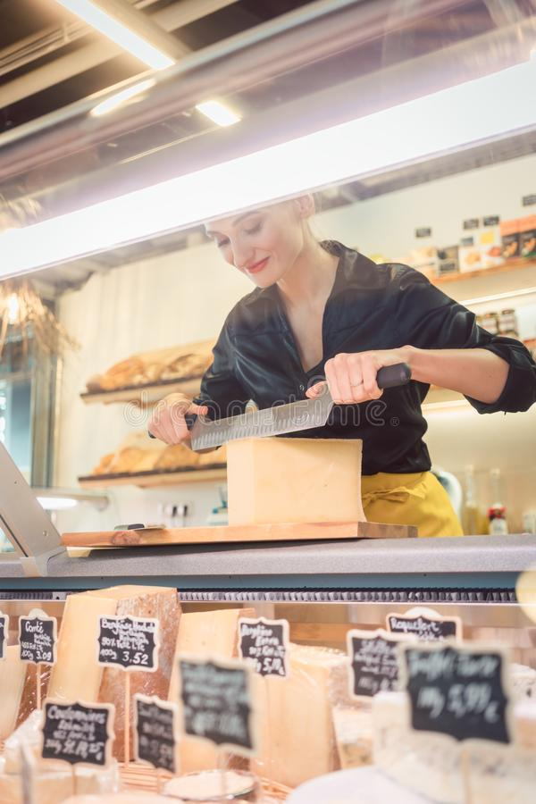 Ungt shoppa kontoristen i delikatessaffär som klipper ost royaltyfria bilder