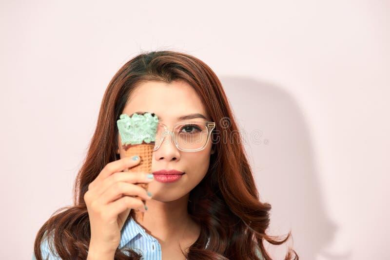 Ungt skämtsamt i glasögon som täcker ögat med glasskotten på ljus bakgrund arkivbild