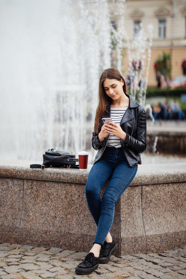 Ungt skönhetkvinnaanseende vid springbrunnen och använda hennes smartphone med kaffe utomhus i stadsgatan stads- stil arkivbild