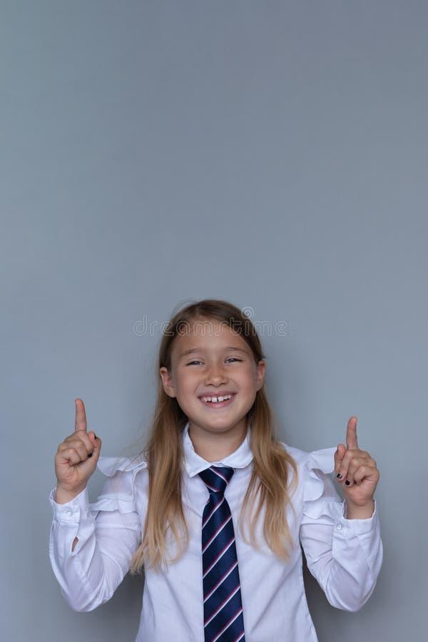 Ungt skolbarn som pekar upp ståenden arkivfoton