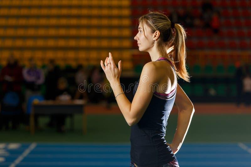 Ungt slankt försök för idrottskvinnastartlängdhopp arkivfoto