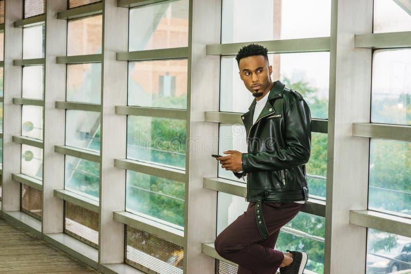 Ungt smsa för afrikansk amerikanhögskolestudent på mobiltelefonen royaltyfria foton
