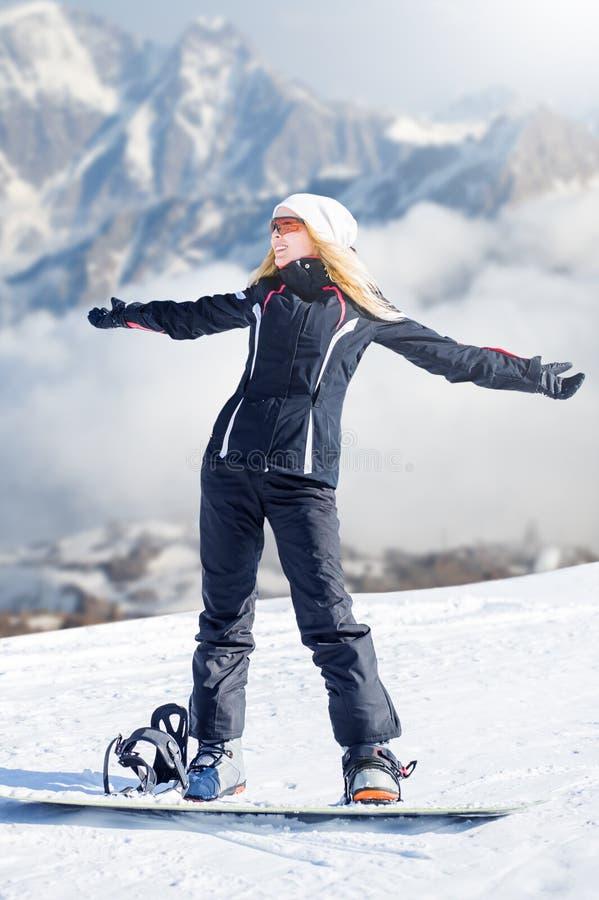 Ungt snowboarderanseende för vuxen kvinna på en snowboard en fot i omfamningen av annan i snön e royaltyfria bilder