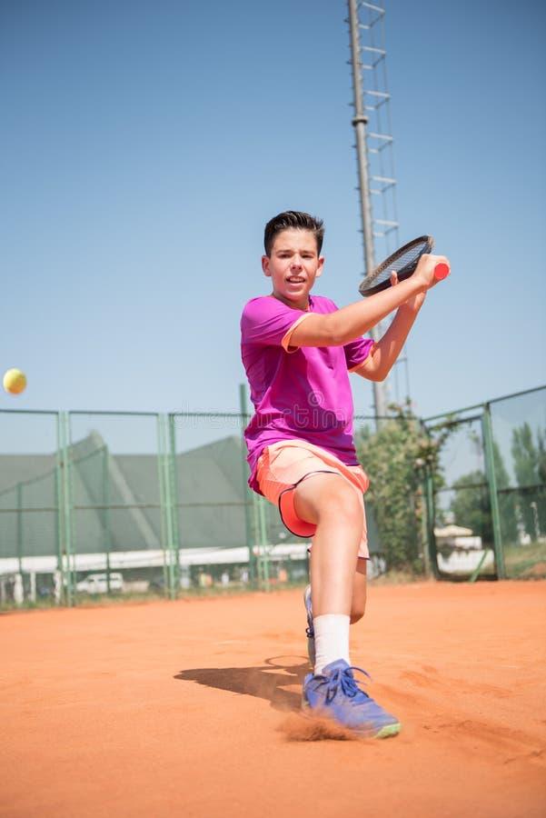 Ungt spela för tennisspelare som är backhand-, och glidljud på en solig dag royaltyfri foto