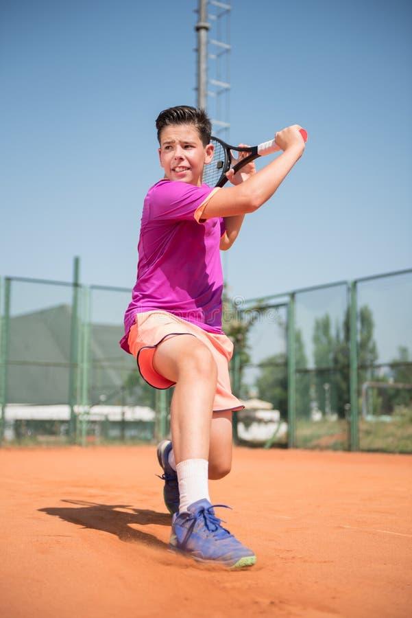 Ungt spela för tennisspelare som är backhand-, och glidljud på en solig dag fotografering för bildbyråer