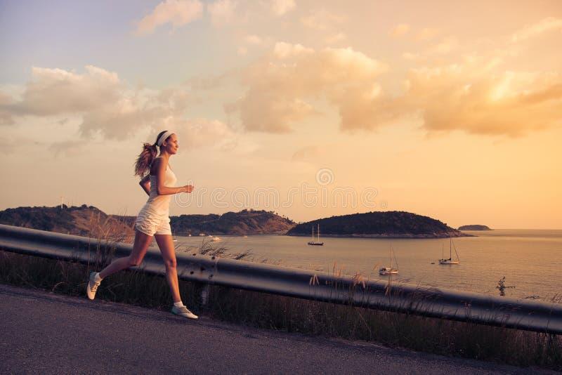 Ungt sportigt köra för kvinna som är utomhus- på solnedgången royaltyfria foton