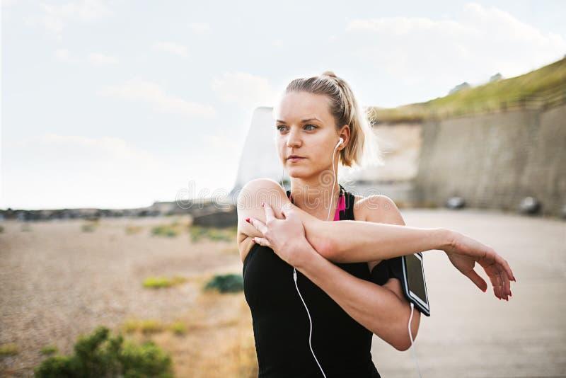 Ungt sportigt kvinnalöpareanseende på stranden utanför och att sträcka fotografering för bildbyråer