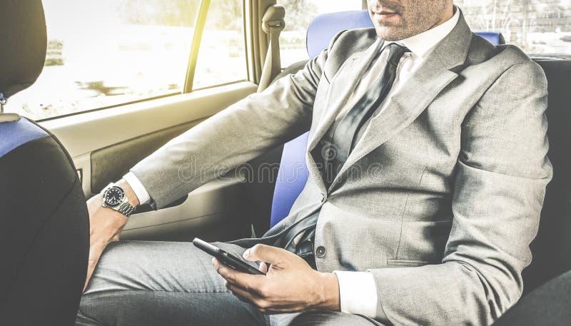 Ungt stiligt affärsmansammanträde i taxitaxi med telefonen royaltyfri bild