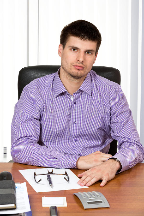Ungt stiligt affärsmansammanträde på hans skrivbord royaltyfria foton