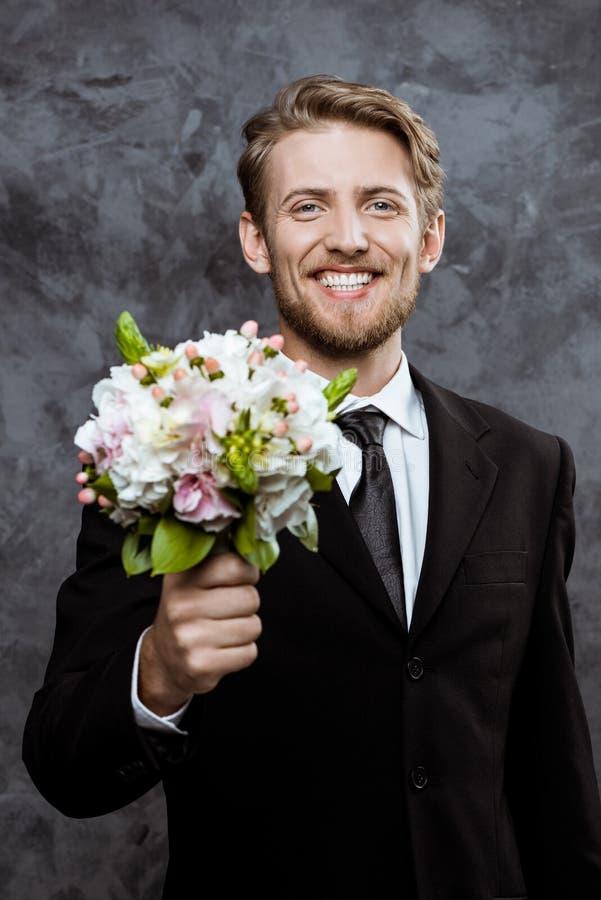 Ungt stiligt le för brudgum som rymmer den brud- buketten över grå bakgrund royaltyfri foto