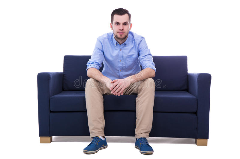 Ungt stiligt mansammanträde på soffan på vit arkivbild